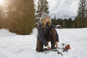 Woman putting snowshoes on