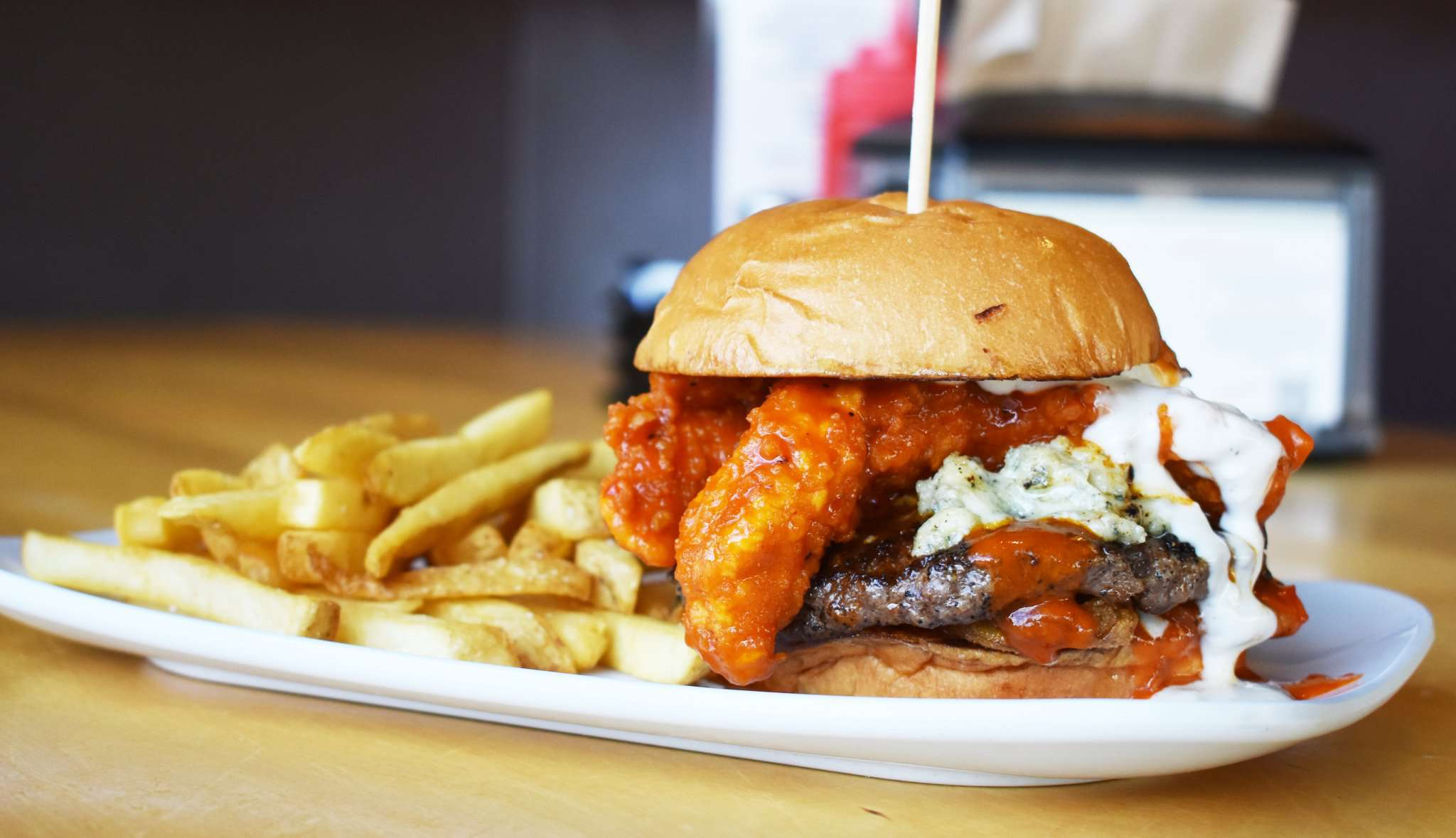 burger with buffalo chicken strips and blue cheese next to some french fries