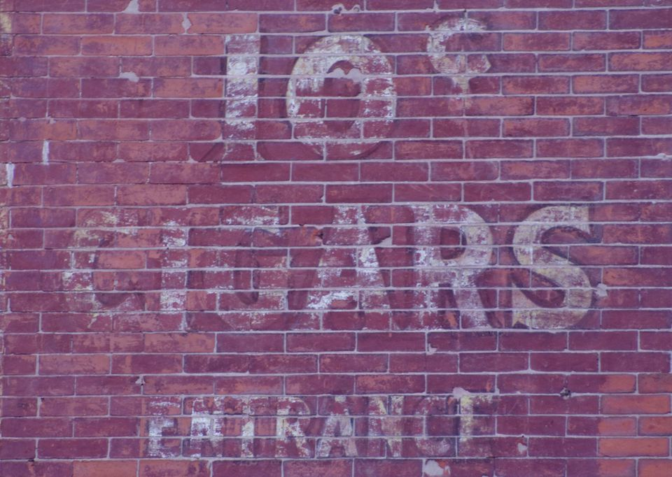 An old weathered billboard in downtown Boston, large white letters painted on a brick wall.