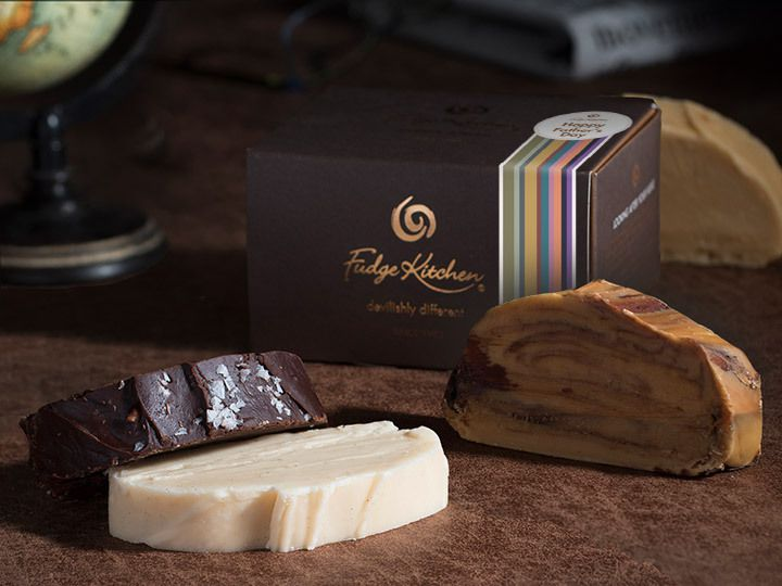 three different kinds of fudge in front of a brown closed box and one slice of fudge behind the box