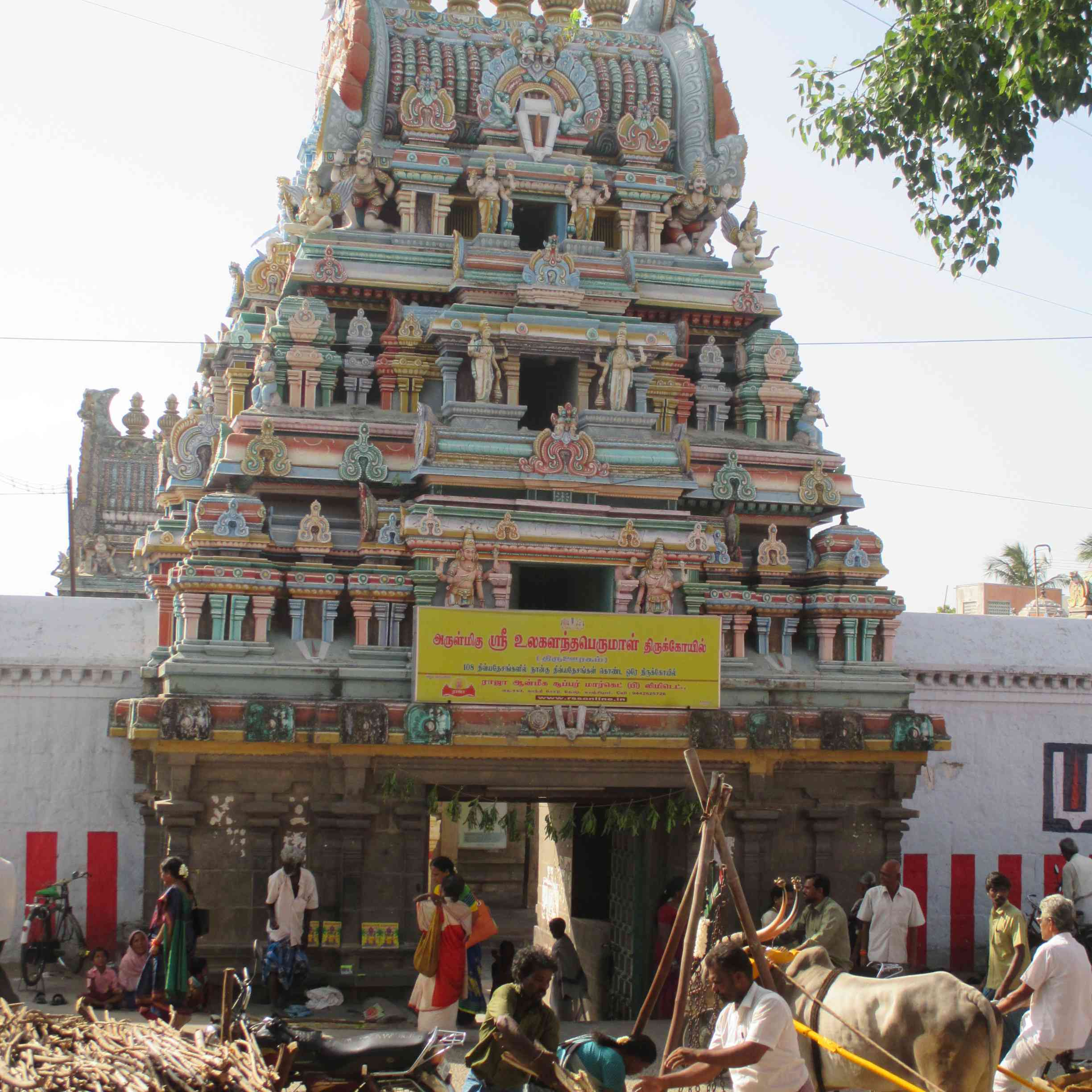 people standing in front of the three tiered Raja Gopuram of Ulagalantha Perumal Temple