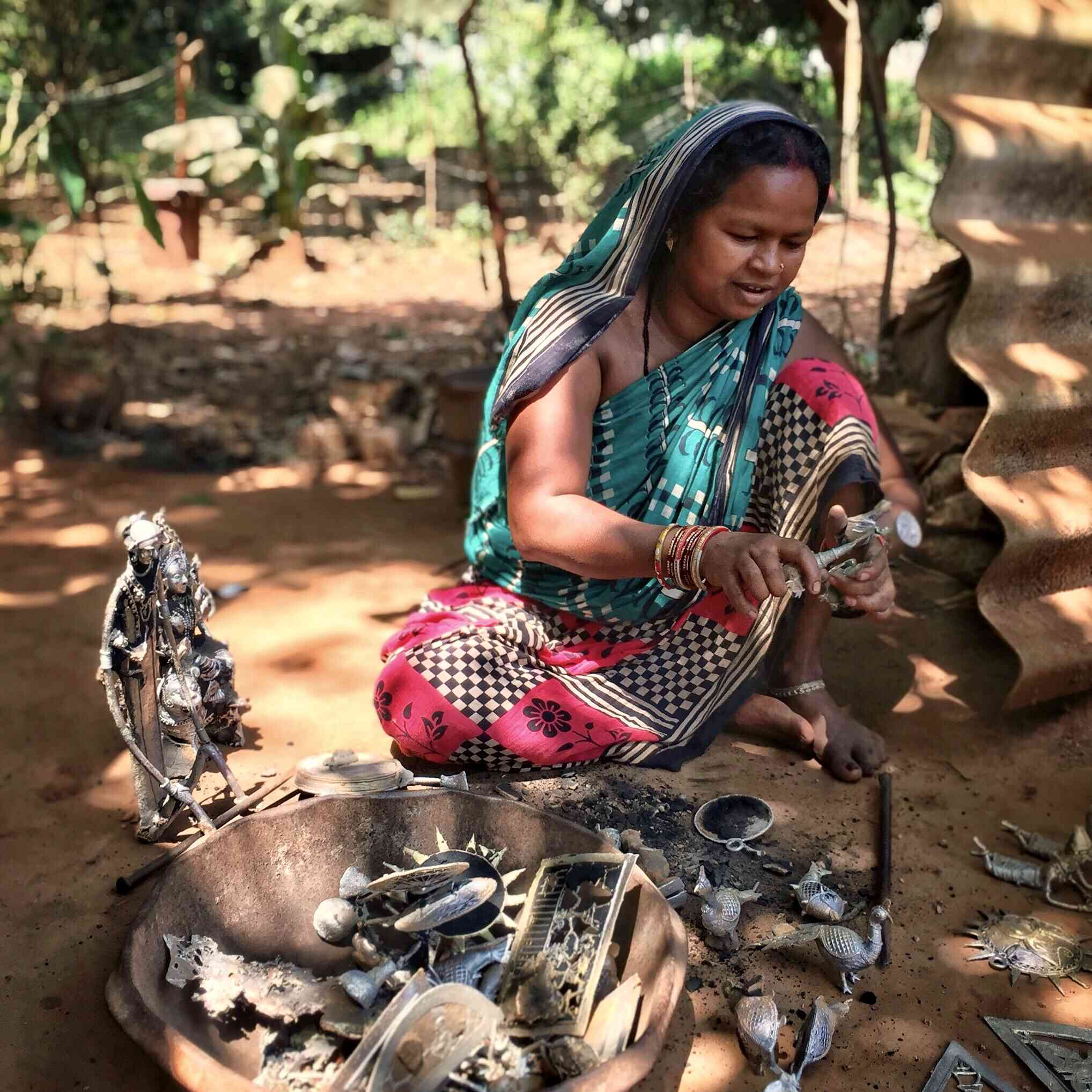 Female Dhokra artisan in Odisha sitting on the ground