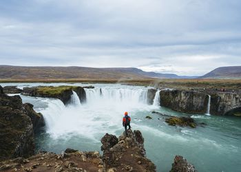 Man looking at view of epic waterfall in Iceland