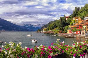 a view of Lake Como in italy with flowers in the foreground