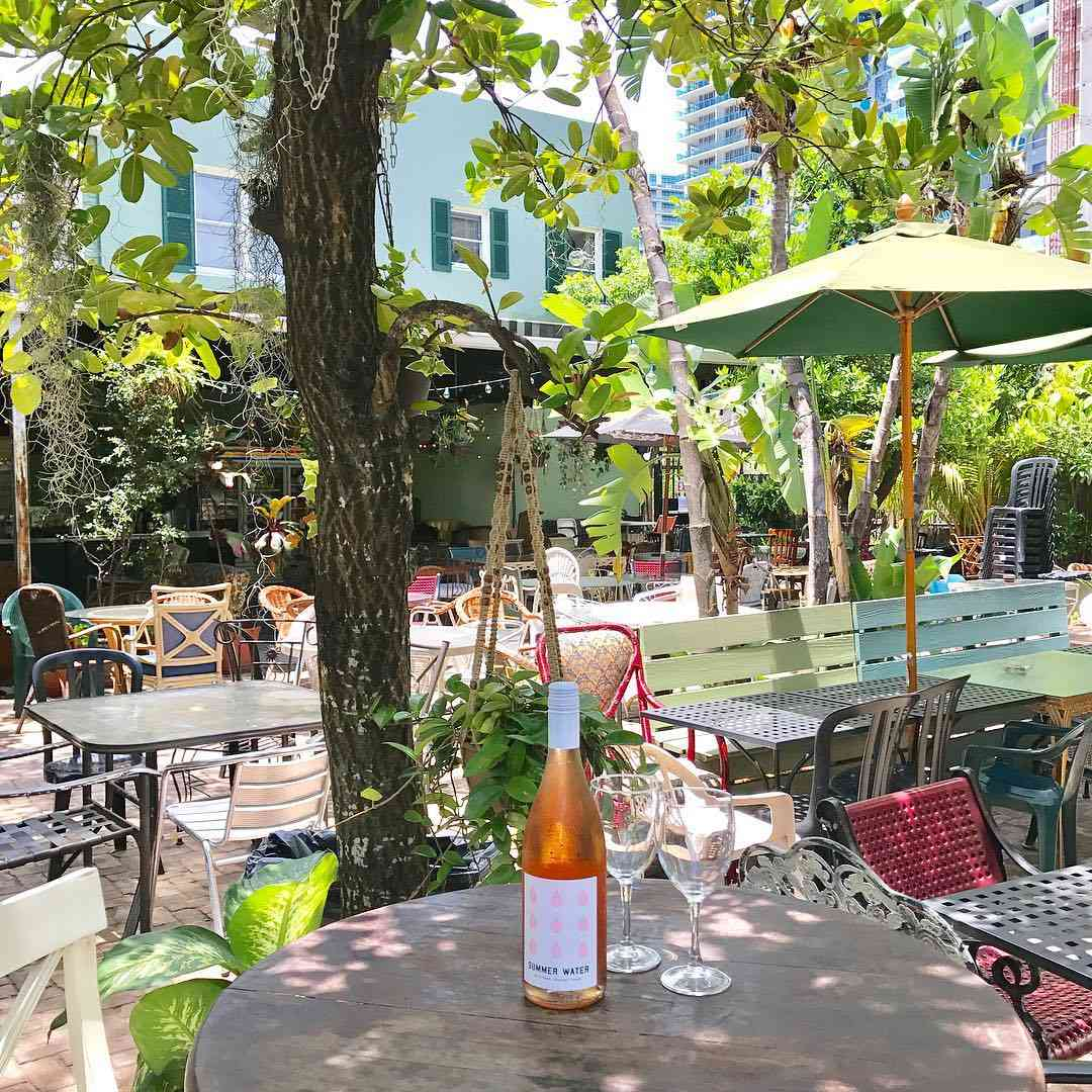 Unopened bottle of rosé with two wine glasses on an outdoor table in a patio with mismatched tables and chairs and a variety of trees