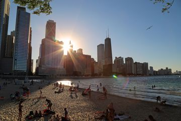 Beachgoers relax and watch the sunset at Chicago's Olive Park Beach.