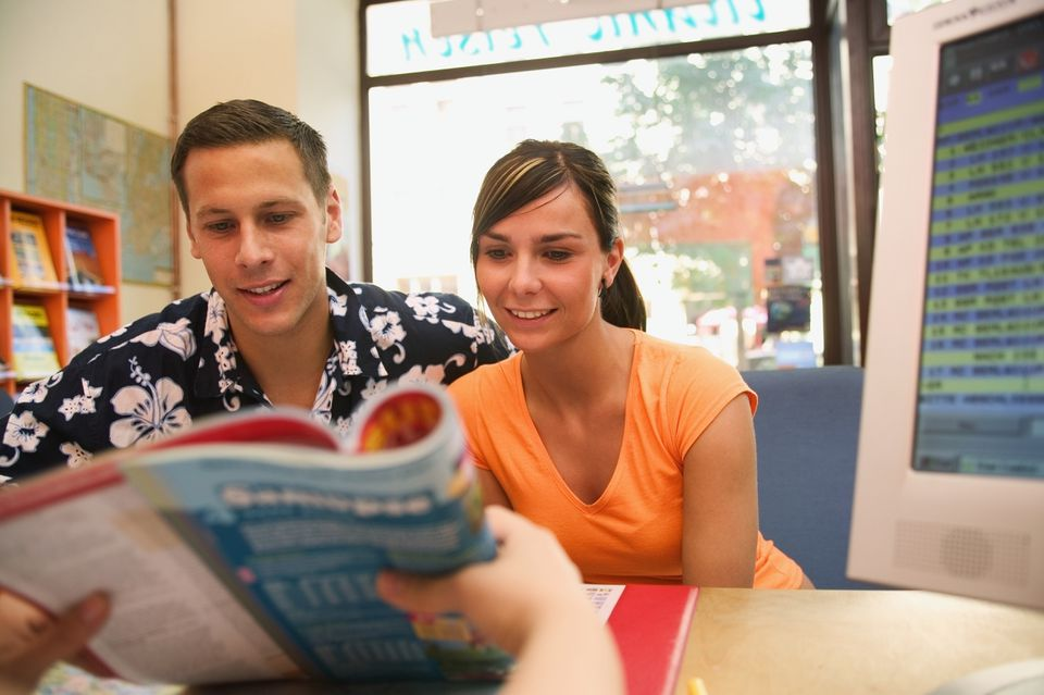 Young couple looking at brochure shown by travel agent