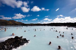 Blue Lagoon geothermal open air spa pool in Iceland, under blue sky streaked with clouds.