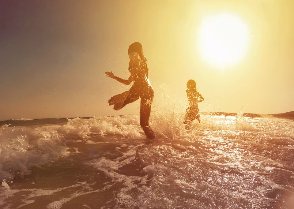 Happy girls running to the sea on a beautiful sunset