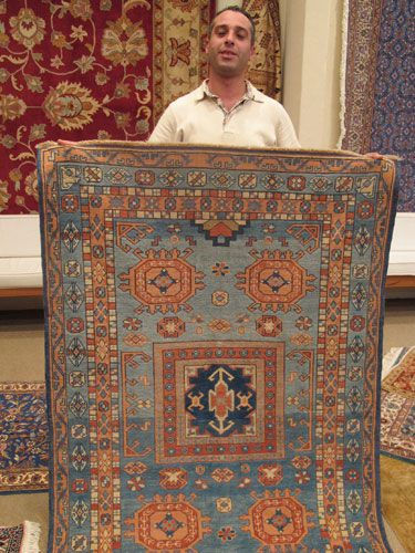 a man holding up a turkish rug
