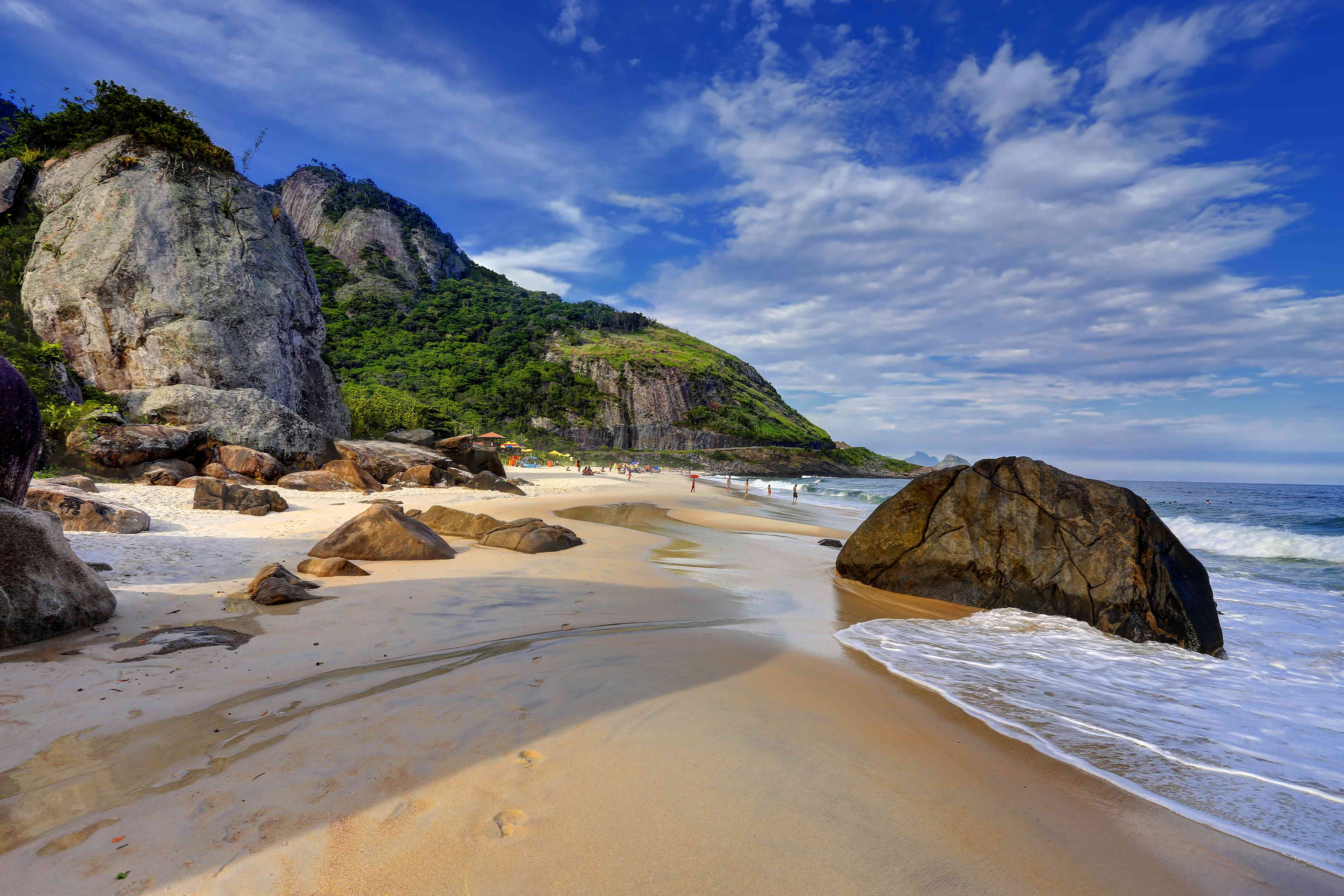 large rocks on a beach in Brazil with a mountain in the background