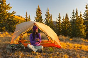 woman sitting outside a tent in fall