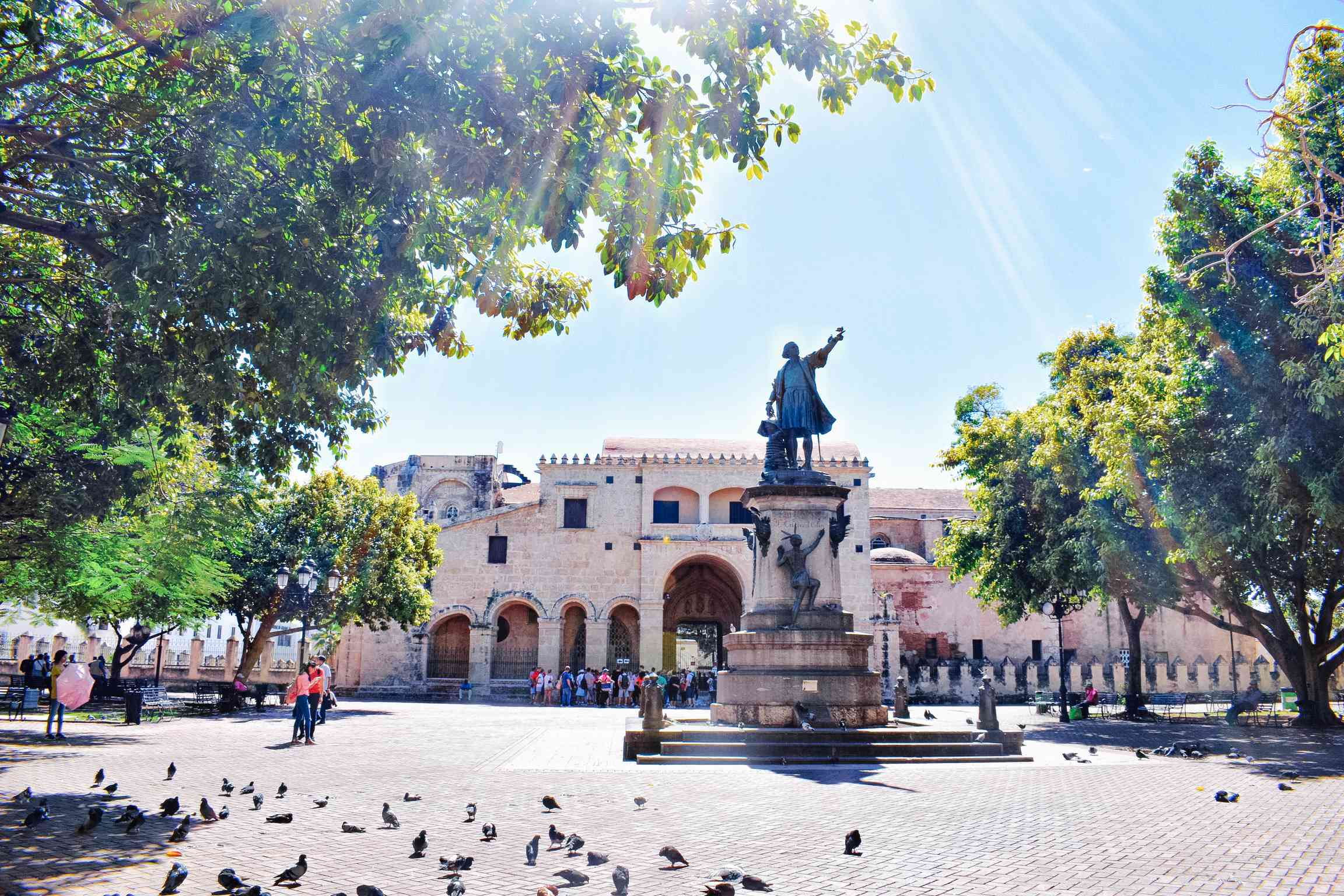 Sun shining down in the main square of Parque colon of old buildings and a statue