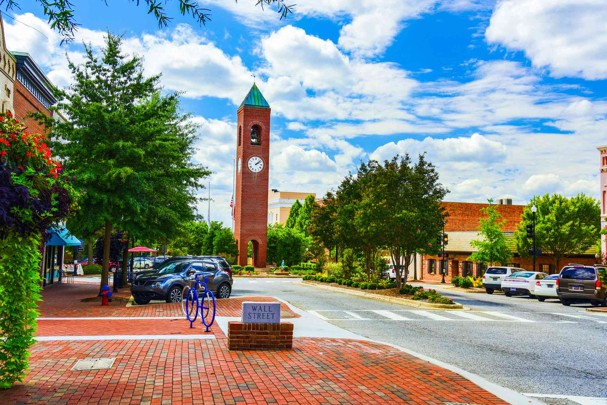 Highly saturated imaged of a brick clocktower on a tree lined street