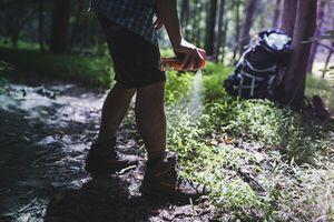 Hiker spraying bug spray on legs