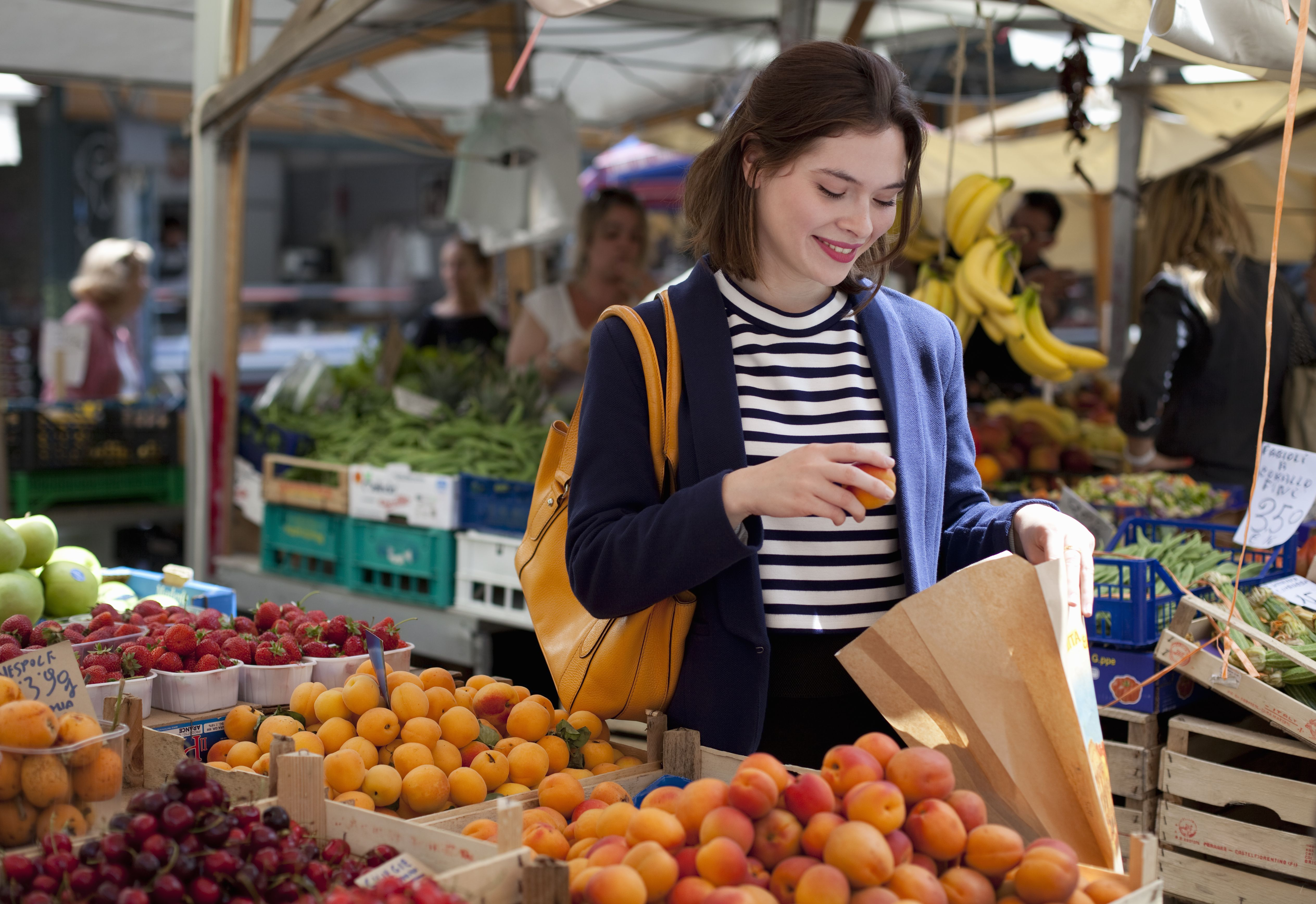 young woman choosing apricots from fruit stand
