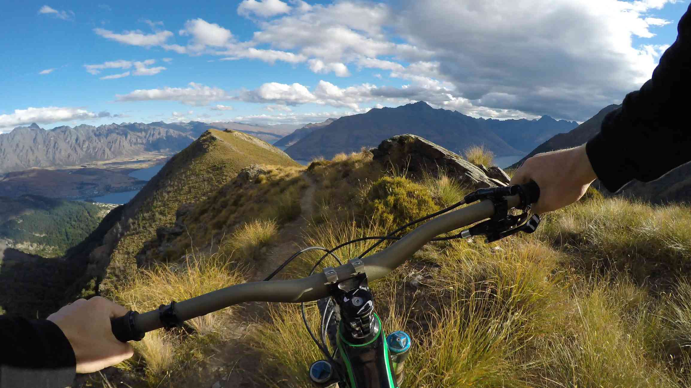 hands gripping bike handlebars riding along grassy hill with mountains in background