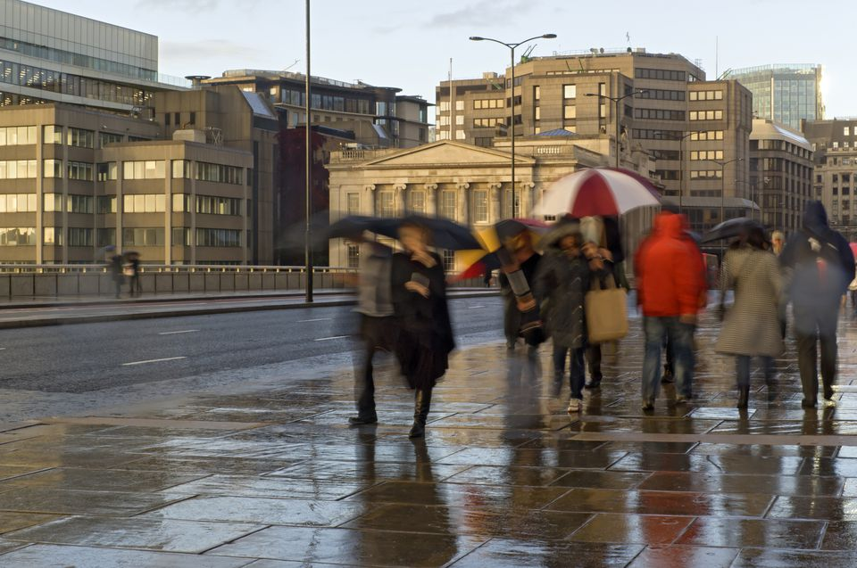 People walking on pavement in rain, London, UK