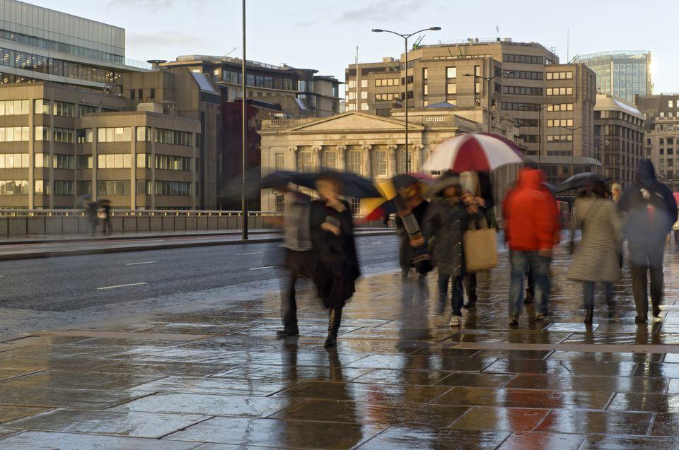 Gente caminando sobre el pavimento bajo la lluvia, Londres, Reino Unido
