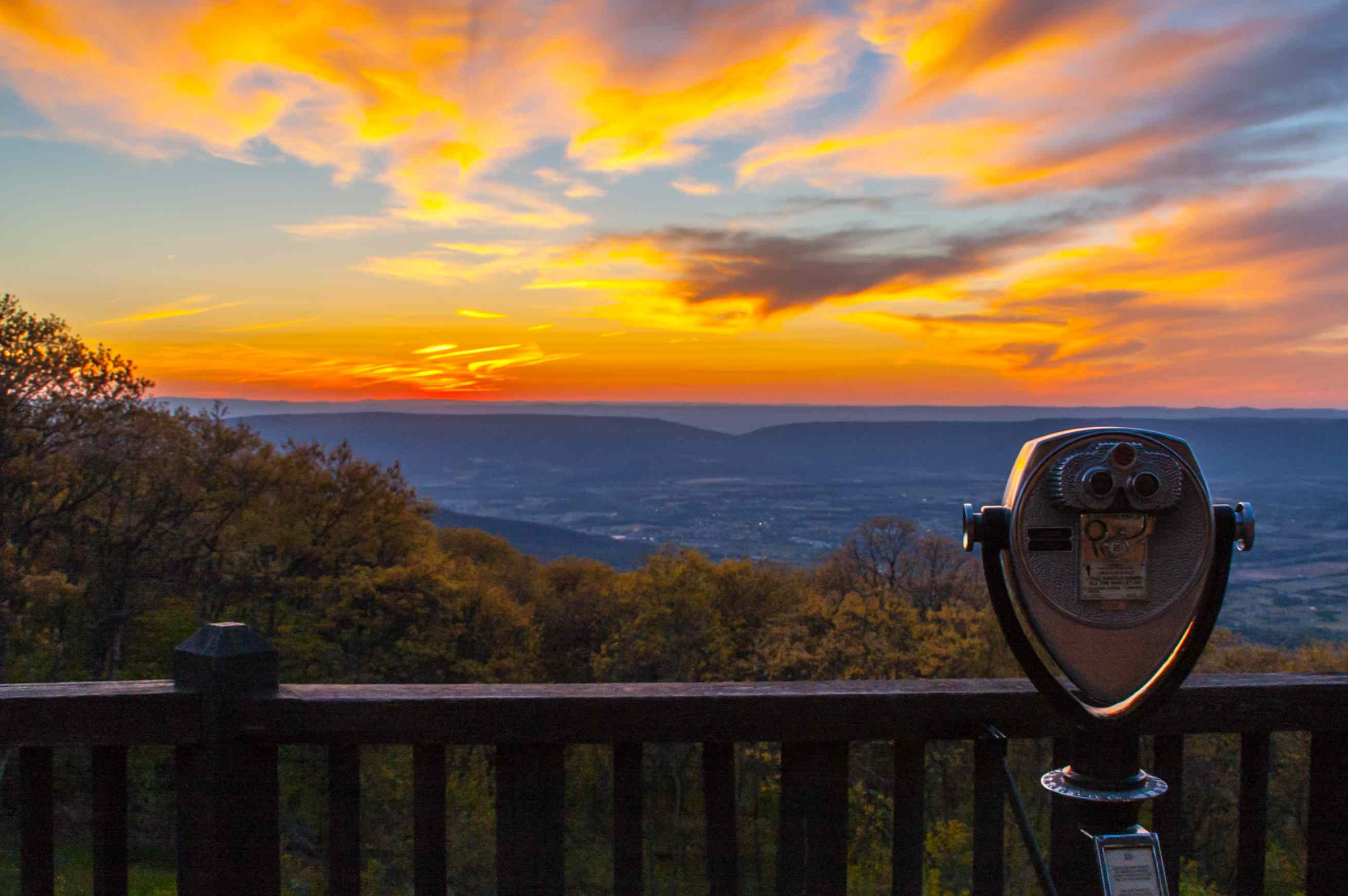 Vivid sunset over the Shenandoah Valley seen from an observation deck with a guardrail and coin-operated binocular