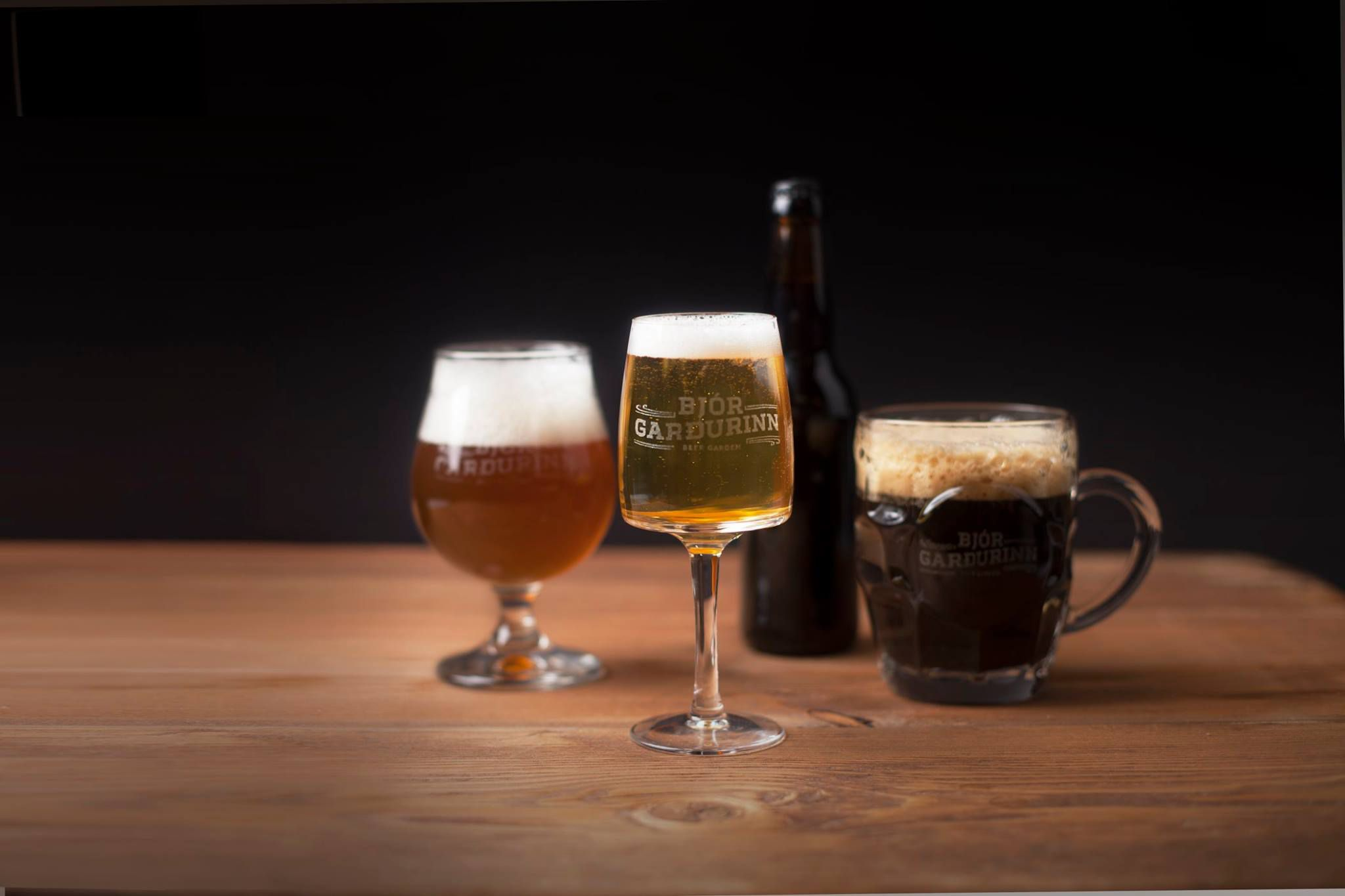 Three glasses filled with different kinds of beers and one beer bottle on a wooden table