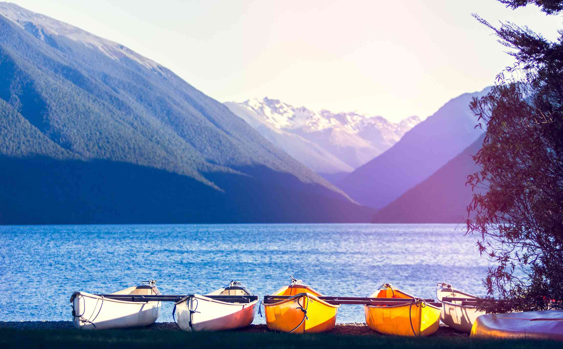 mountains and lake with white and yellow kayaks in foreground
