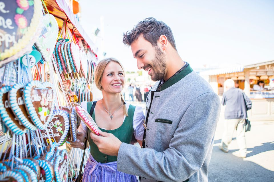 Young Couple Standing At Market Stall at Oktoberfest in Germany