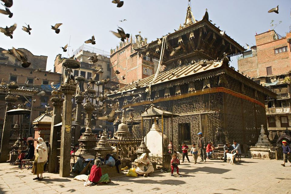 Seto Machendranath temple, close to Durbar Square, Kathmandu, Nepal. Pagoda style gilt roofed temple in a monastic courtyard now housing shops and market stalls.