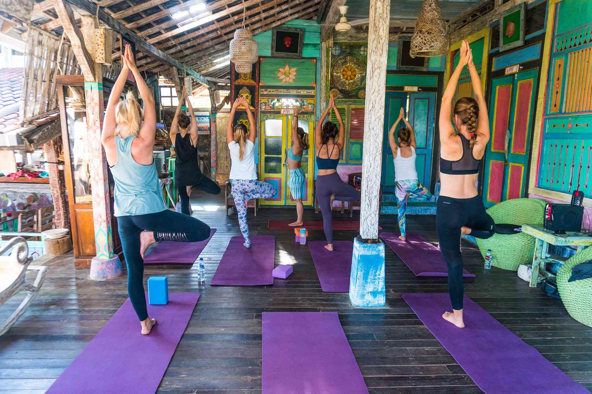 Small yoga class of six people doing tree pose in a colofully decorate room in Bali