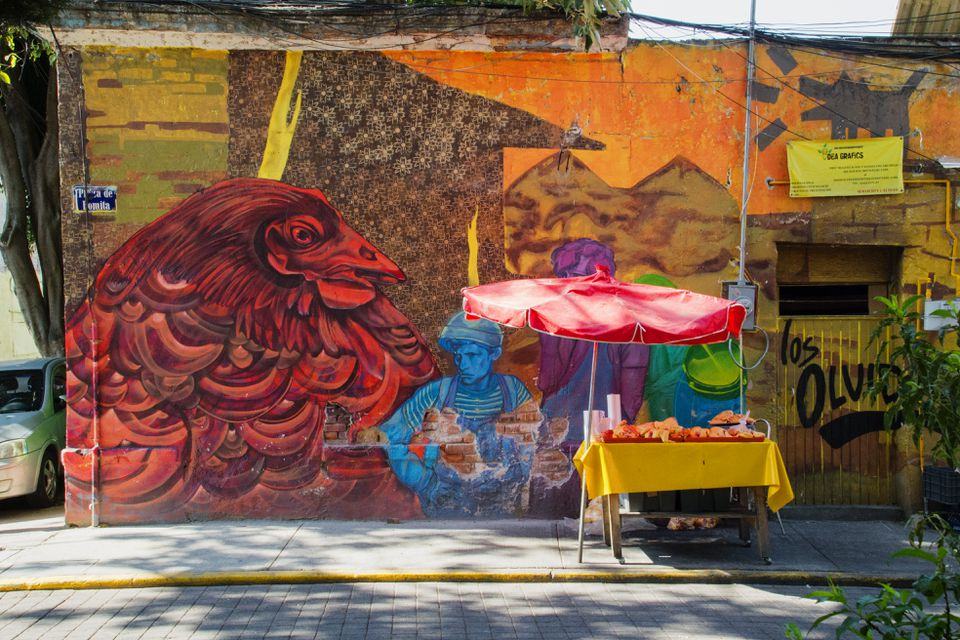 A fruit cart parked in front of a wall with a large mural on it