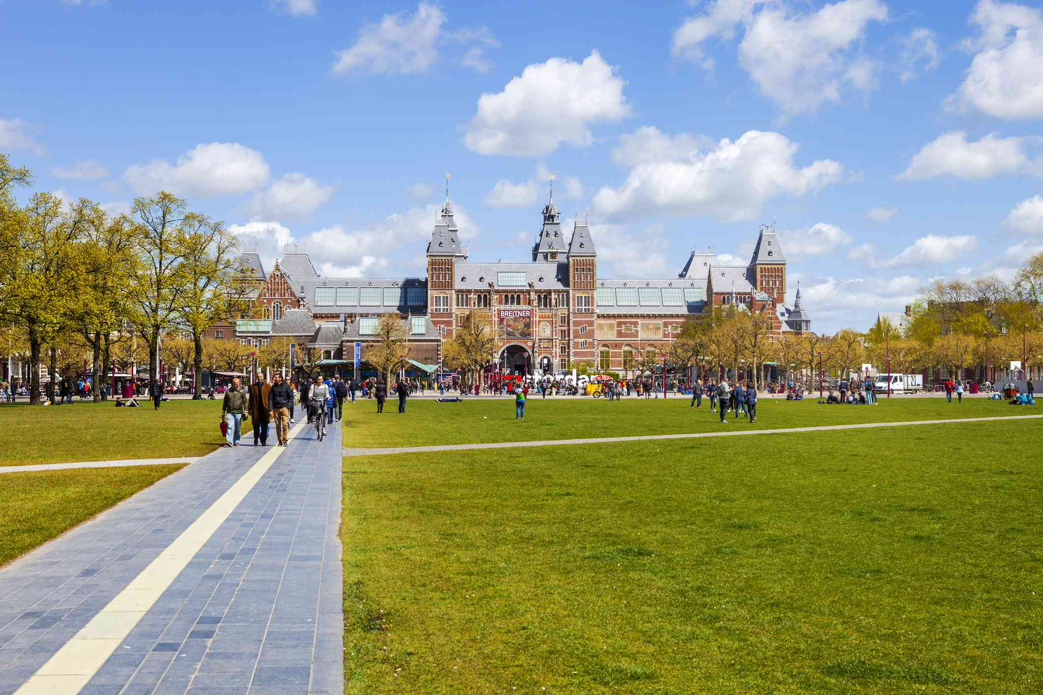 People, grass field and view of Rijksmuseum, Museumplein