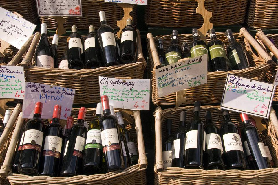 Wine shop in Rue Mouffetard displaying baskets of bottles