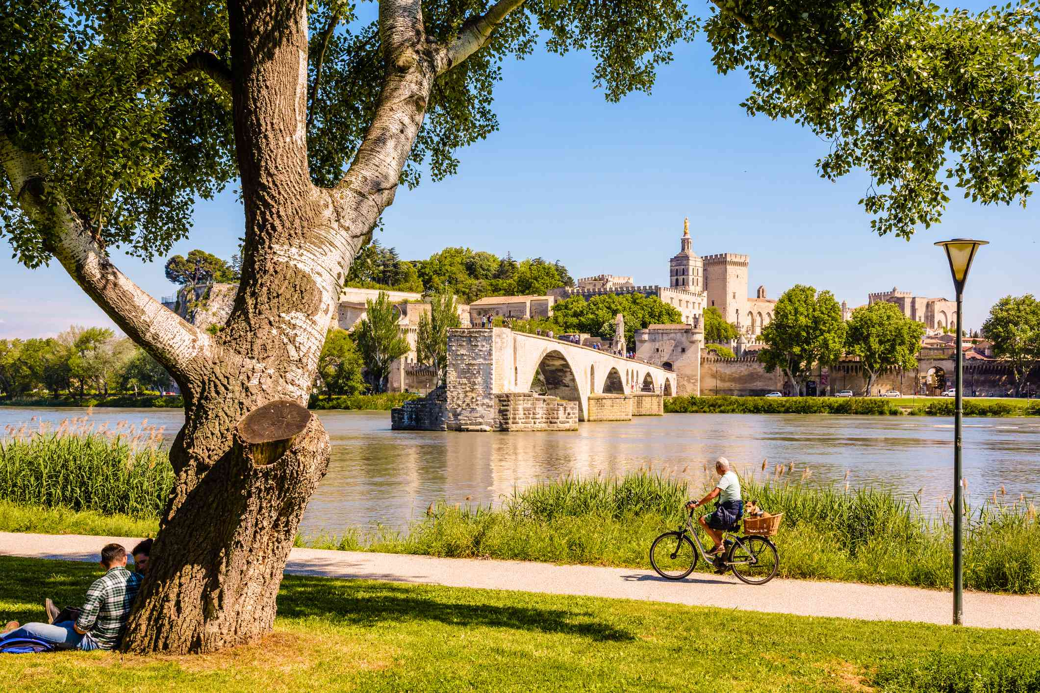 The banks of the Rhone on a sunny day, opposite the Avignon bridge and the Papal palace in Avignon, France.