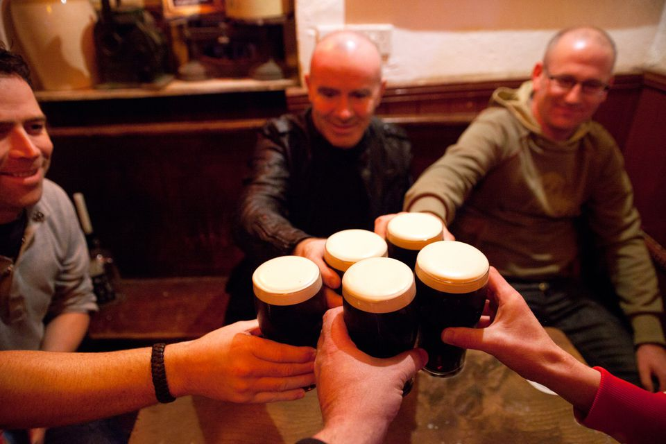 Group of men in pub raising glasses of stout in celebration.