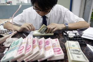 A bank employee working with American and Chinese currency