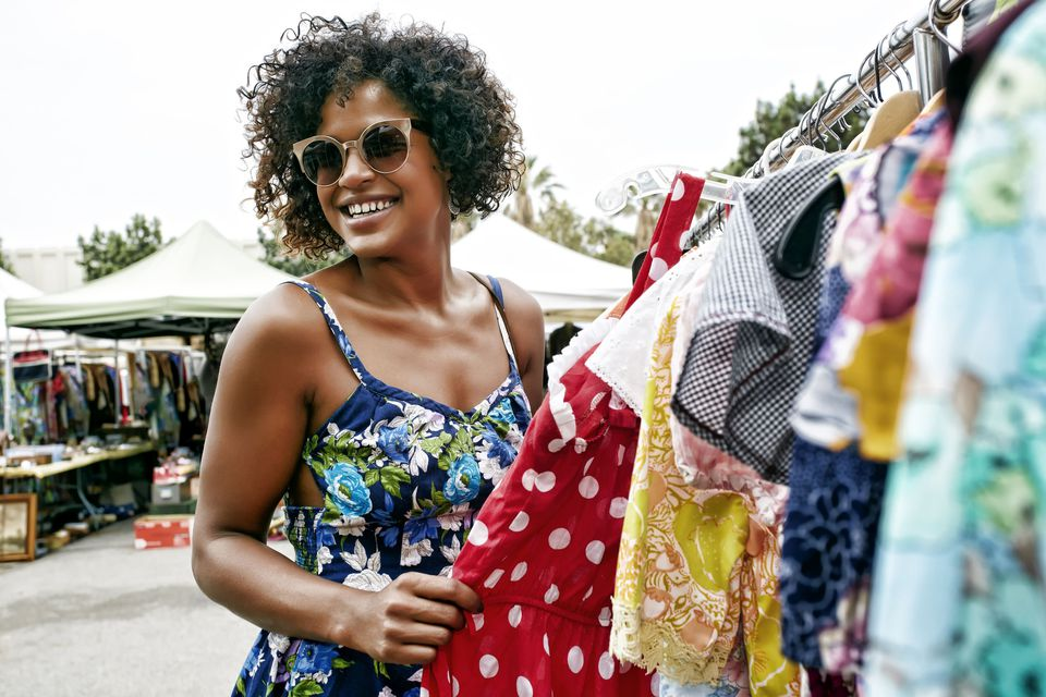 A shopper browses a rack of vintage clothes at an outdoor flea market