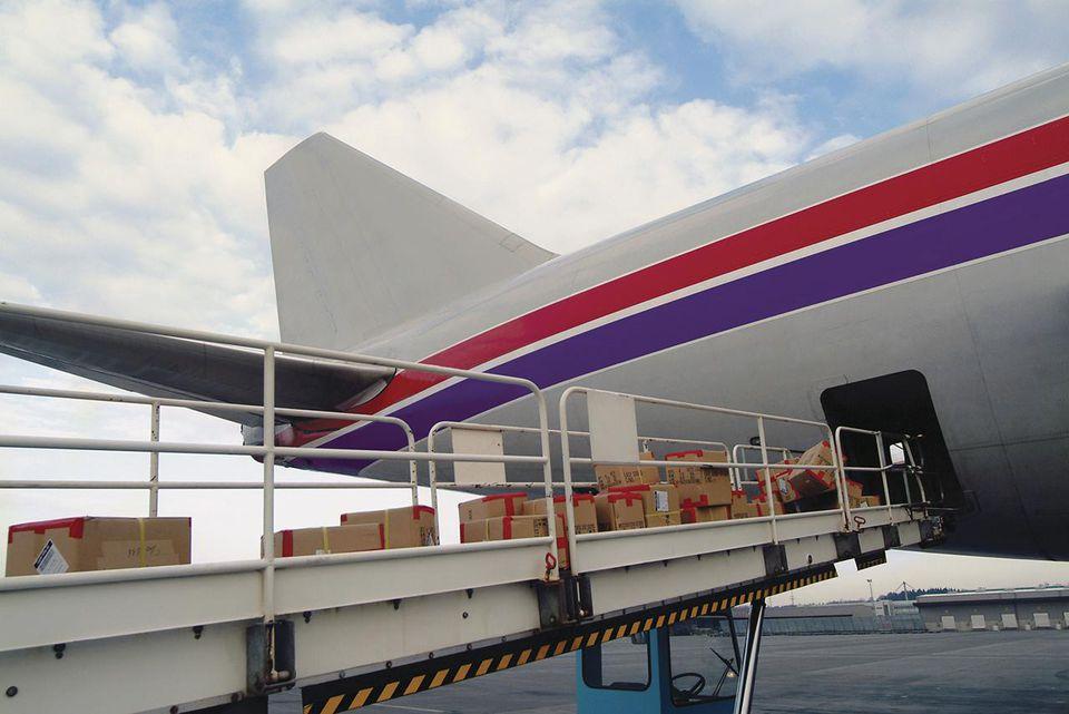 Contenedores de cartón en una cinta transportadora que se cargan en la parte trasera de un avión de carga