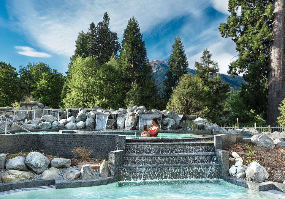 Couople in a ppol with evergreen trees behind a rocky water feature