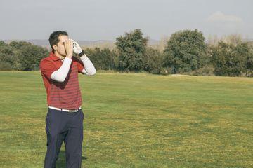 Golfer using a laser rangefinder, golf course