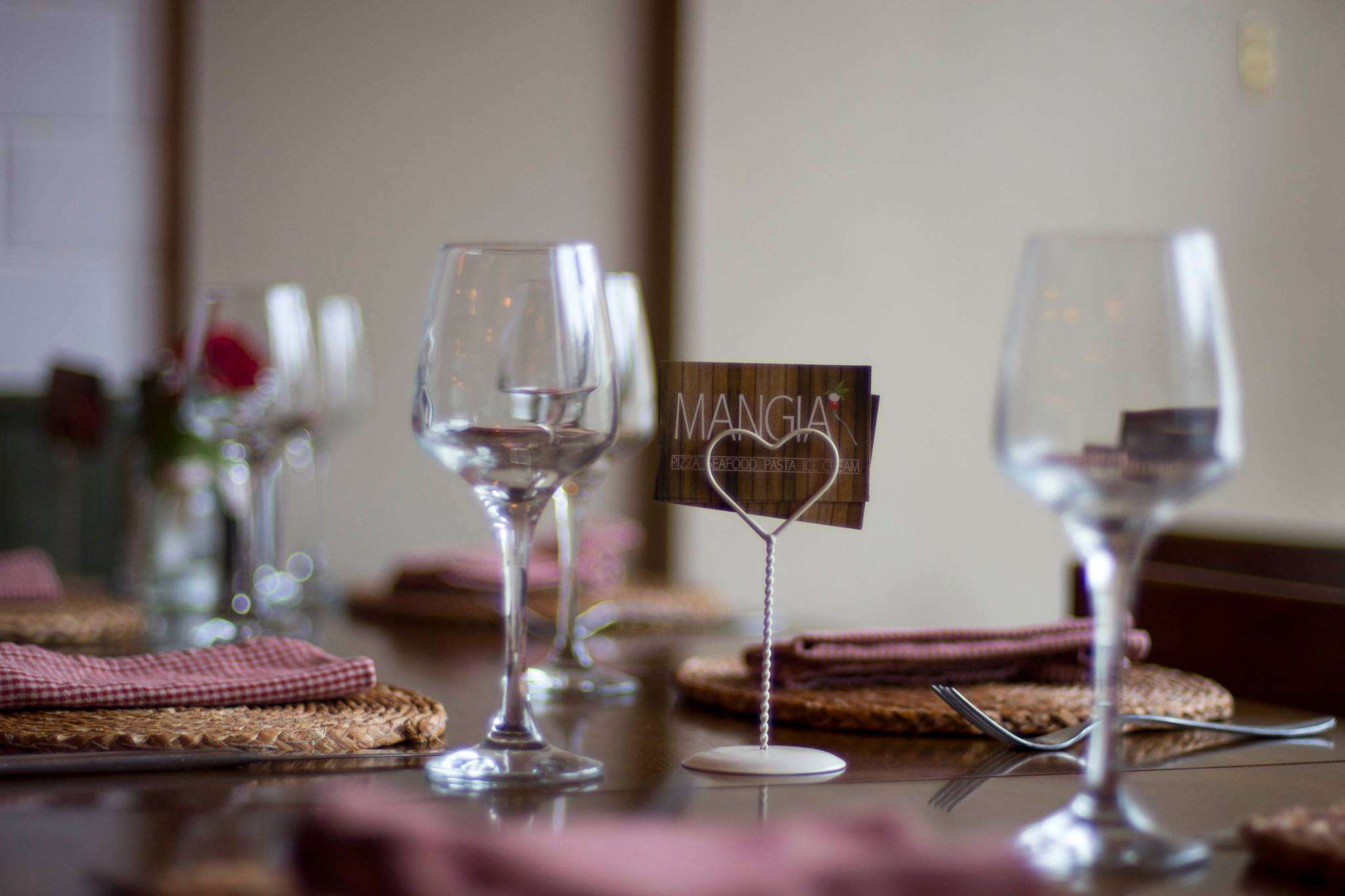Table set with wine glasses, folded napkins, and card stand with a Mangia business card
