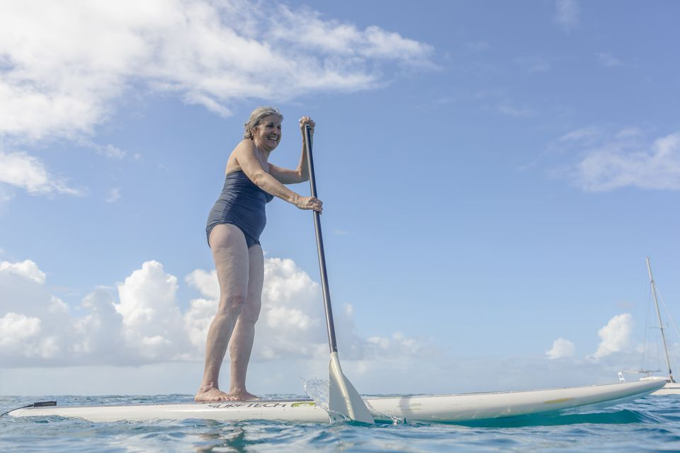 Senior woman standing on a paddle board on the ocean