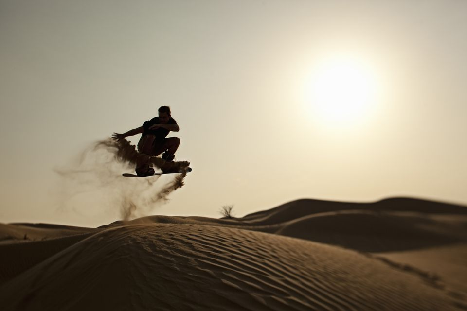 man sandboarding in the desert