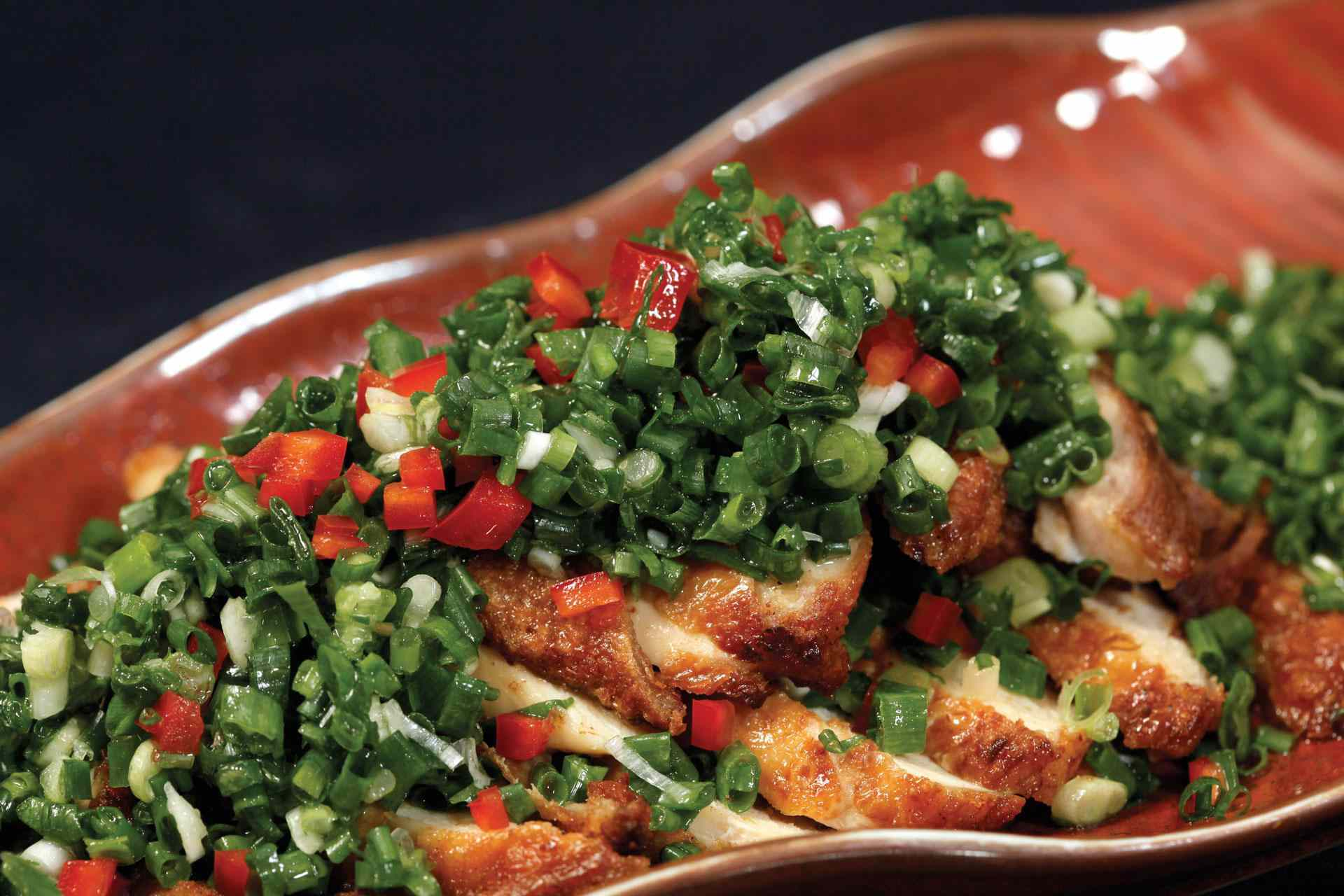 sliced, grilled chicken on a ceramic plate with a pile of scallions