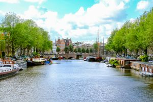 Boats docked on the side of a canal in Amsterdam on a sunny day