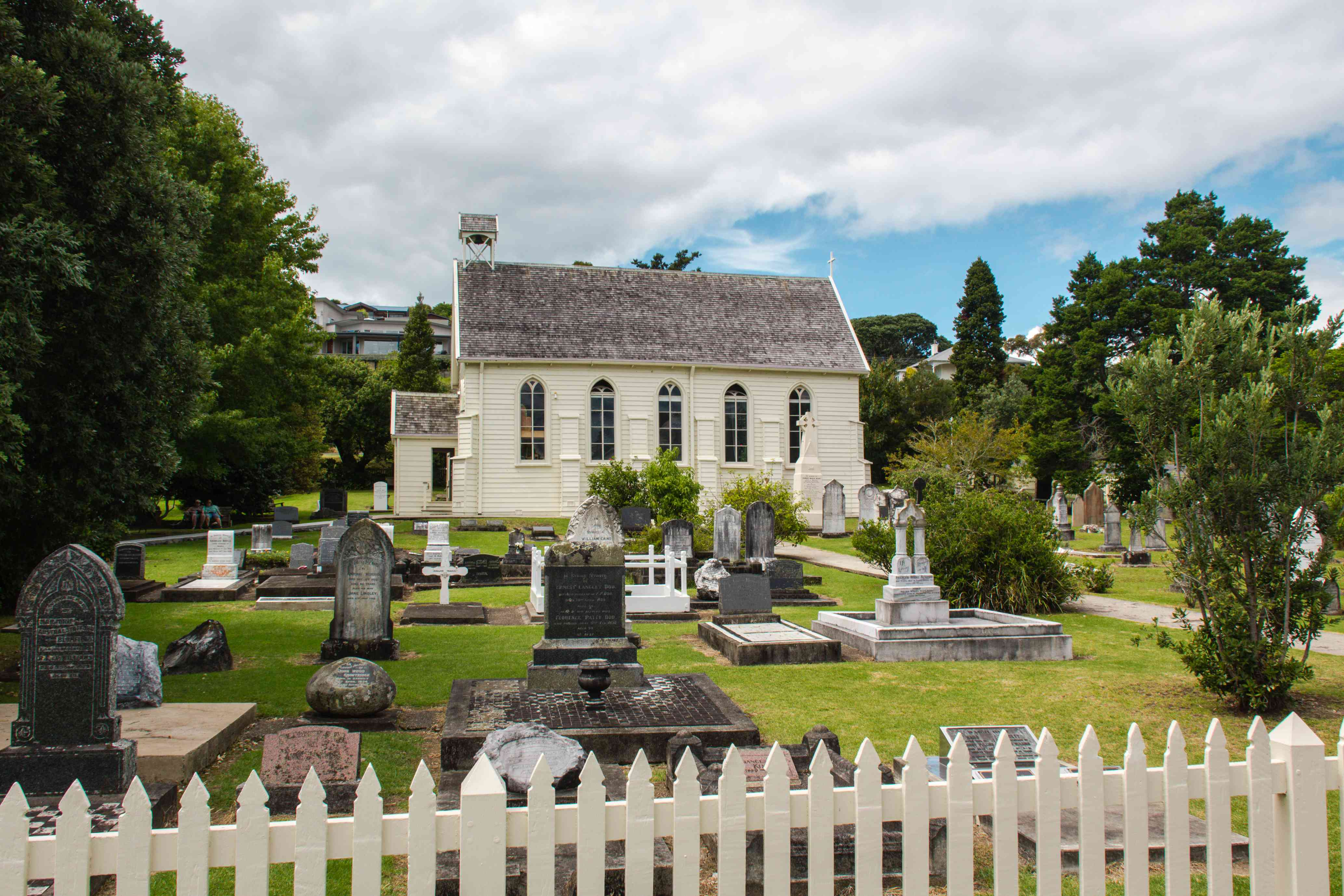 White wooden church with graves and white picket fence