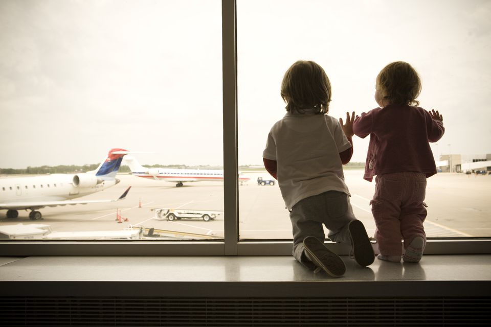 Two children excitedly watch as planes land at aitport