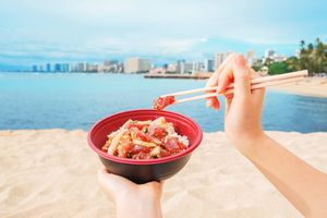 A woman holding a bowl of poke on the beach in waikiki