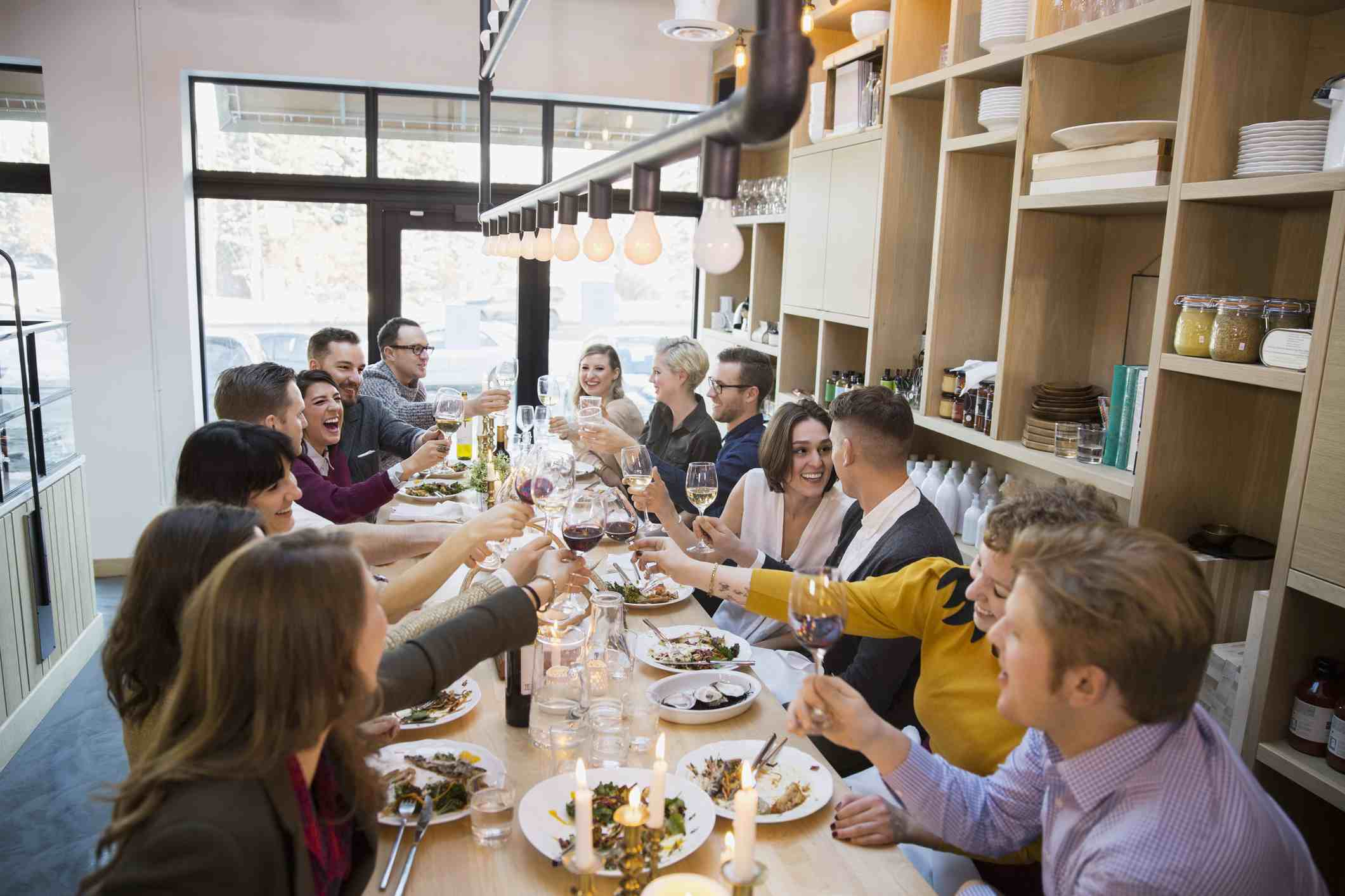 Friends Toasting Wine Gles At Restaurant Table