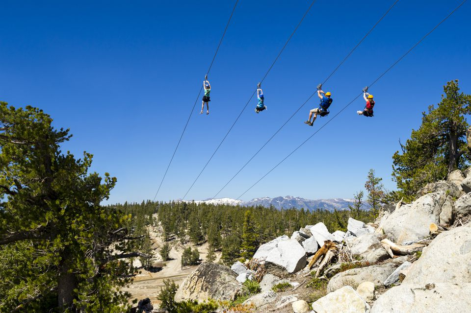 Family riding zip line, South Lake Tahoe, California, USA