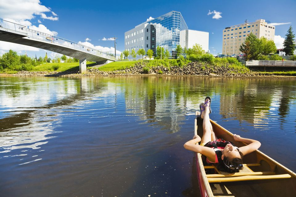 A young woman relaxes in a canoe in Fairbanks